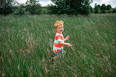 Toddler boy laughing while walking through a long grassy field outside - p1166m2148791 by Cavan Images