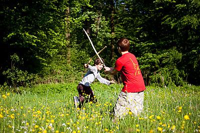Jungen beim Stockkampf im Park - p1195m1138134 von Kathrin Brunnhofer