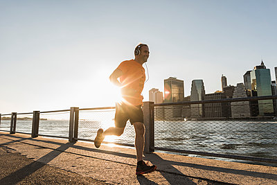USA, Brooklyn, man jogging in front of Manhattan skyline in the evening - p300m1205223 by Uwe Umstätter
