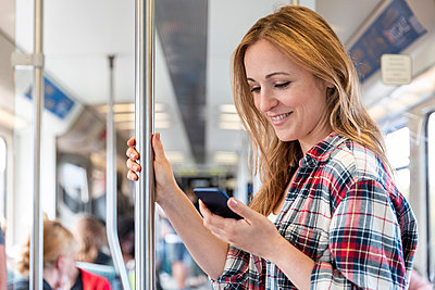 Smiling woman looking at her smarphone on the subway, Berlin, Germany - p300m2156830 by William Perugini