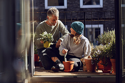 Father and daughter planting together on balcony - p300m2188916 by Maya Claussen
