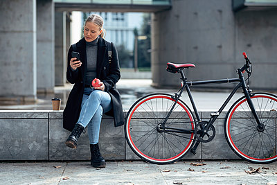 Young woman using mobile phone while sitting on retaining wall by bicycle - p300m2256202 by Josep Suria