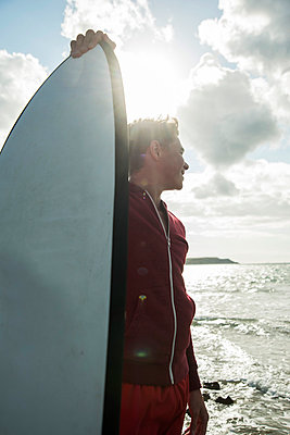 France, Brittany, Camaret-sur-Mer, teenage boy with surfboard at the ocean - p300m981656f by Uwe Umstätter