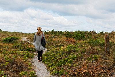 Woman walking, rear view - p312m2080477 by Pernille Tofte