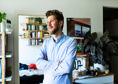 Young man with crossed arms in home office - p341m2178614 by Mikesch