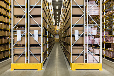 Empty narrow aisle amidst racks at distribution warehouse - p426m2018882 by Maskot