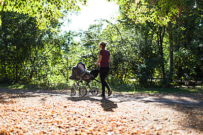 Woman with stroller in park - p795m2020889 by Janklein