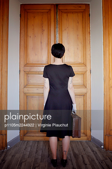 Woman in black dress and suitcase - p1105m2244922 by Virginie Plauchut