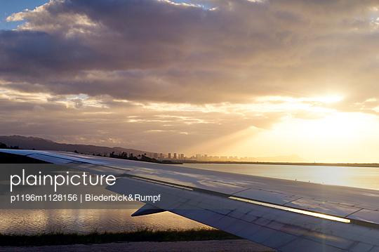 Blick aus dem Flugzeug auf die Morgensonne über Honolulu, Oahu, Hawaii - p1196m1128156 von Biederbick & Rumpf