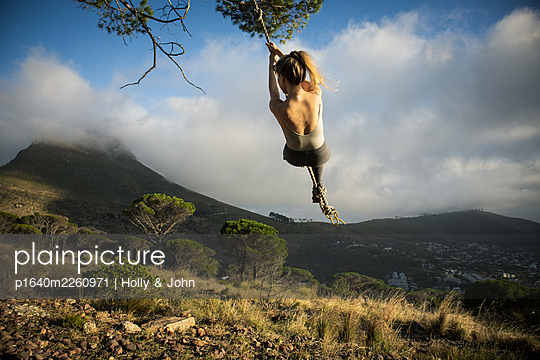 Blond woman swings on a rope in the mountains - p1640m2260971 by Holly & John