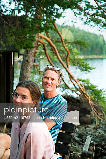 Mature couple relaxing by lake - p352m2119763 by Lena Katarina Johansson