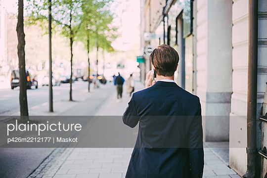 Rear view of businessman talking on phone in city - p426m2212177 by Maskot