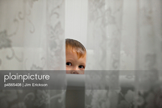 Young boy looking through lace curtains as he takes a bath - p4565408 by Jim Erickson