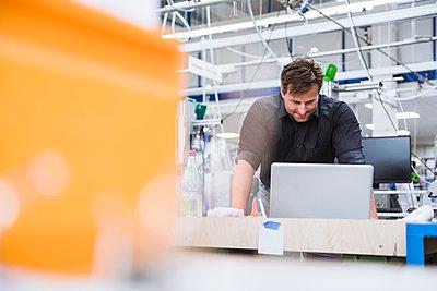 Man using laptop in factory - p300m2197532 by Daniel Ingold