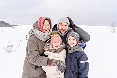 Happy family standing on snow covered land against sky during vacation - p300m2251375 by Ekaterina Yakunina