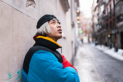 Thoughtful male hipster looking up against wall in city during winter - p300m2252620 by Jose Carlos Ichiro