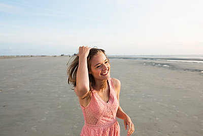 Young woman on St. Peter-Ording beach - p341m1480708 by Mikesch