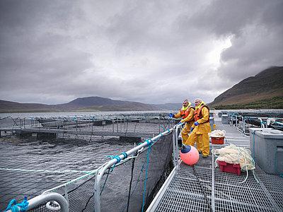 Workers talking at fish farm - p42917327f by Monty Rakusen