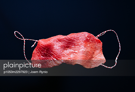 Roulade. Slice of raw beef in the shape of a medical mask - p1053m2297923 by Joern Rynio