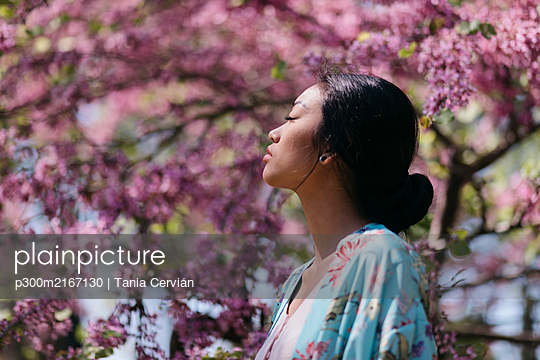 Beautiful young woman with blooming cherry tree in a public garden in spring - p300m2167130 by Tania Cervián