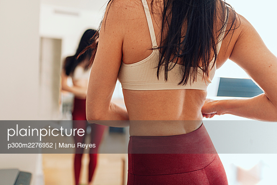 Woman in bra and yoga pants standing at home - p300m2276952 by Manu Reyes