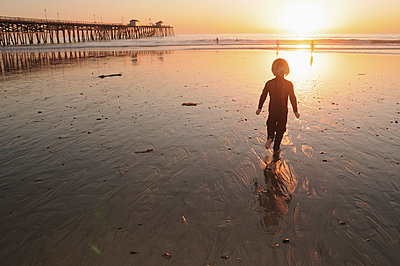 little boy in a wetsuit running on the beach at sunset next to San Clemente pier - p1014m993698 by Kristianne Koch Riddle