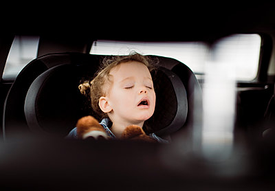 Cute girl with mouth open sleeping in car seen through vehicle seat - p1166m1568966 by Cavan Images