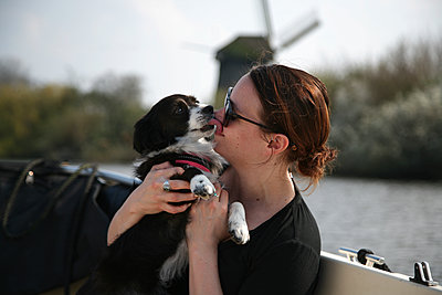 A young woman getting licked by her dog on a boat ride. - p1166m2111815 by Cavan Images