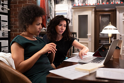 Female designers analyzing drafts on laptop - p1166m2227675 by Cavan Images