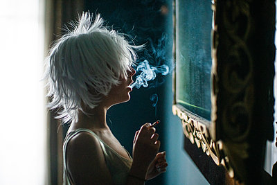 Smoking woman with white hair takes a look in the mirror - p1321m2223401 by Gordon Spooner