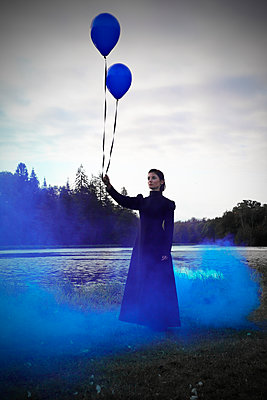 Woman with black dress in a blue smoke - p1521m2215014 by Charlotte Zobel