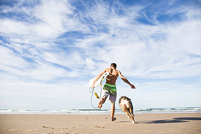 Man carrying surfboard running with dog on the beach - p300m1204549 by Andrés Benitez