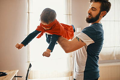 Father playing with his little son dressed up as a superhero - p300m1581564 von Zeljko Dangubic