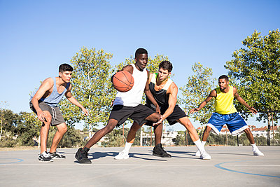 Young men playing basketball and dribbling ball on sports ground - p300m2139486 von Andrés Benitez