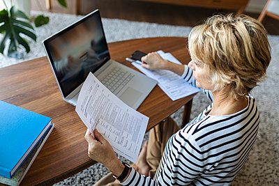 Mature woman with documents using laptop at home - p300m2144948 by Valentina Barreto