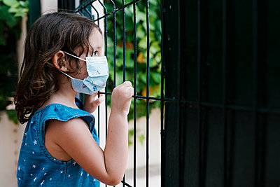 Close-up of girl wearing mask looking through fence while standing in yard - p300m2213953 by Ezequiel Giménez