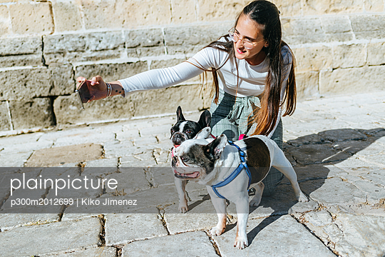 Young woman using smartphone, taking a selfie with her dogs - p300m2012699 von Kiko Jimenez