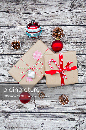 Wrapped Christmas presents, Christmas baubles and fir cones on wood - p300m977899f by Larissa Veronesi