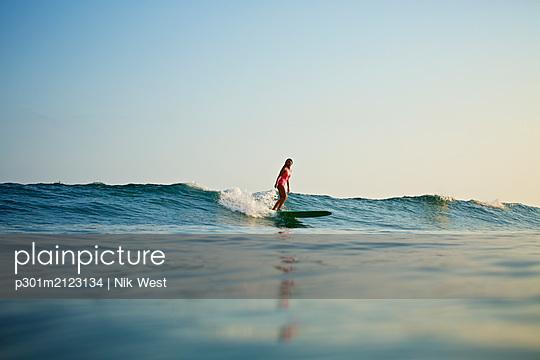 Female surfer riding ocean wave - p301m2123134 by Nik West