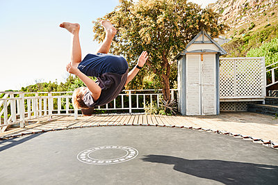 Little boy jumping on trampoline - p1640m2244880 by Holly & John