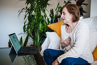 Woman talking with doctor through video call on laptop while sitting at table home - p300m2264960 by Eva Blanco