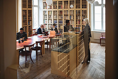 Lawyers working in library seen through glass in library - p426m1148137 by Maskot