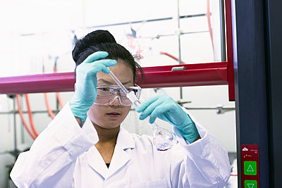 Female scientist using pipette and volumetric flask in lab - p429m1027726f by Sigrid Gombert