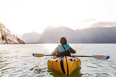 Woman packrafting, Howe Sound bay, Squamish, Canada - p429m2036907 by Alex Eggermont