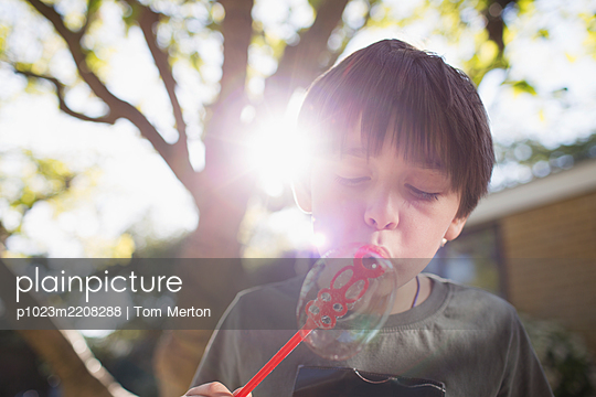Boy blowing bubbles in sunny backyard - p1023m2208288 by Tom Merton