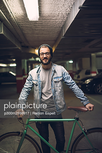 Young man standing in park house with his fixie bike - p300m2166917 by Ramon Espelt