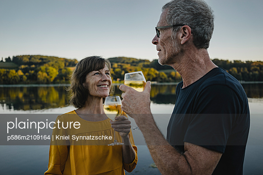 Mature couple drinking white wine at Lake Baldeneysee - p586m2109164 by Kniel Synnatzschke