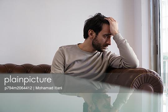 Sad man sat on sofa hand on head looking away  - p794m2064412 von Mohamad Itani