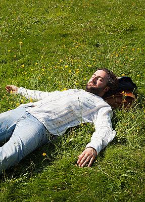 Mann schläft auf einer Wiese - p1008m1170000 von Valerie Schmidt
