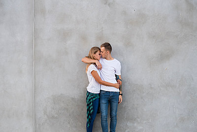Romantic couple embracing while standing against gray wall - p1166m1209873 by Cavan Images